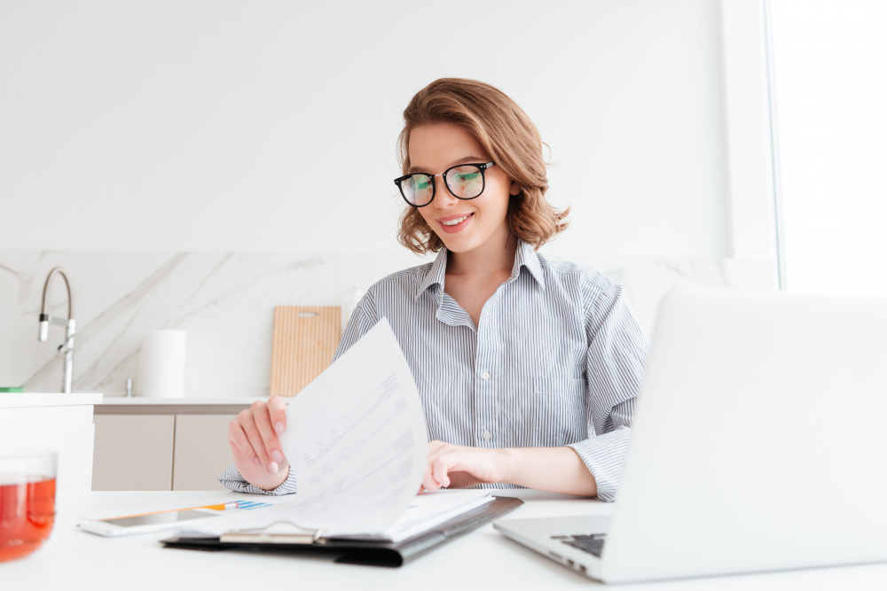 cheerful-woman-glasses-reading-new-contract-while-working-kitchen